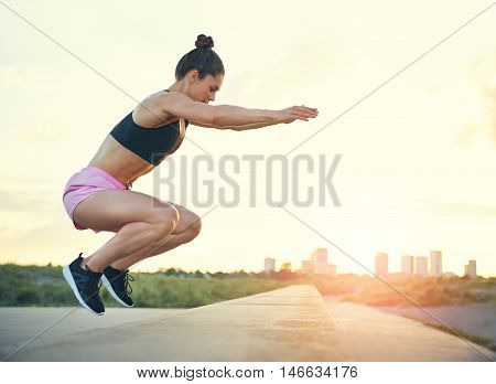 poster of Healthy fit young woman doing crossfit exercises leaping on and off a low stone wall at the side of a promenade with the rising sun and cityscape in the distance