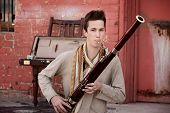 stock photo of sherwani  - Handsome young Caucasian man in Indian attire plays a Bassoon - JPG