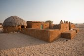stock photo of mud-hut  - A traditional thatched roof mud hut and home in the desert - JPG