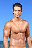 stock photo of fitness man body  - sexy caucasian fit man posing in a beach - JPG