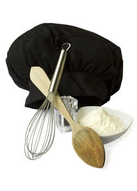 image of kitchen utensils  - Some kitchen utensils for cooking including a hat a bowl and a wooden spoon isolated in white - JPG