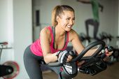 Beautiful Young Woman Doing Cardio On A Stationary Bike While Smiling poster