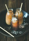 Refreshing Summer Drink. Cold Thai Iced Tea In Bottles With Milk On Plate Over Dark Wooden Backgroun poster