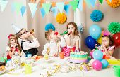 Group Of Smiling Children Playing On The Birthday Party In Decorated Room. Happy Kids Blowing In Pip poster