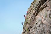 Rock Climbing. A Group Of Young Rock Climbers Climb The Vertical Granite Rock. Extreme Sport poster