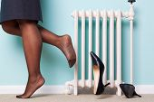 Photo of a businesswomans legs with stockings on kicking her high heel shoes off as she returns home