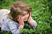 Child Plays Hide And Seek. Cute Child Smile On Green Grass Lawn. Little Girl Relax On Spring Or Summ poster