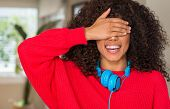 African american woman wearing headphones smiling and laughing with hand on face covering eyes for s poster