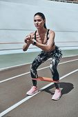 No Ifs Or Buts To Workout. Beautiful Young Woman In Sports Clothing Crouching Using Resistance Band  poster
