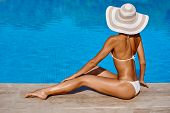 Portrait Of Beautiful Tanned Woman Relaxing In Bikini And Hat In Swimming Pool. Gel Polish Red Manic poster