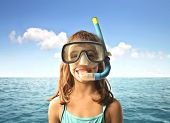 Little girl at the seaside wearing a diving mask