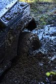 Fragment Of Car Stuck In Dirt, Close Up. Offroad Tire Covered With Mud On Nature Background. Wheel I poster
