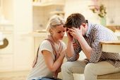 Young woman comforting her unhappy and desperate husband after saying bad news poster