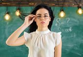 Woman With Long Hair In White Blouse Stands In Classroom. Lady Strict Teacher On Calm Face Stands In poster