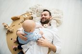 Dad Plays With His Baby Son At Home. Fatherhood And People Concept poster