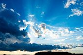 Rays Of The Sun Through The Clouds. Clouds And A Blue Sky With A Sunbeam Shining Through. poster