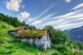 Typical norwegian old wooden houses with grass roofs near Sunnylvsfjorden fjord and famous Seven Sis poster