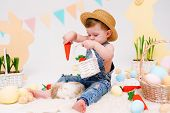Happy Little Boy In Hat Feeds Cute Fluffy Bunny. Friendship With Easter Bunny. Spring Photo With Lit poster