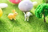 Two Rabbit Toys With Easter Eggs On A Meadow Grass. Yellow Easter Egg Spring Meadow With Two Rabbit  poster