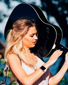 Blonde Woman Having Acoustic Guitar. Female Playing Music On Seaside poster