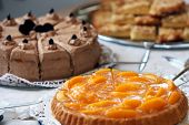 image of foreground  - Dessert buffet at a wedding reception with an assortment of delicious freshly baked cakes and biscuits with focus to a colourful peach tart in the foreground - JPG