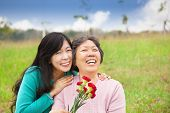 stock photo of carnation  - Smiling daughter and her mother with carnation flower on the grass field - JPG