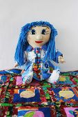 image of rag-doll  - patchwork doll with blue hair sitting on a cheerful patchwork rug - JPG