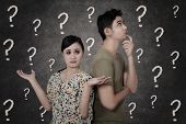 stock photo of punctuation marks  - Confused couple with question marks on blackboard - JPG