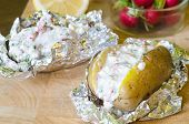 stock photo of grated radish  - Close view of two stuffed potatoes on an aluminum foil with radish - JPG