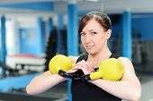 Young Woman Smiling While Lifting Kettle Bell