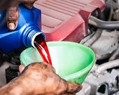 Hand Pouring Transmission Fluid Through Funnel