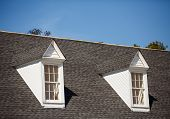 pic of shingles  - Two white wood dormers on a grey shingle roof under blue sky - JPG