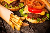 stock photo of fried onion  - Juicy cheeseburger with onion rings and french fries - JPG