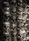 stock photo of catacombs  - Wall full of skulls and bones in the bone chapel in Evora - JPG