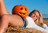 Beautiful Woman Posing On A Bale With Pumpkin