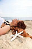The Beautiful Girl Lies On Sea Coast With Shells