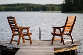stock photo of dock a lake  - A lone wooden chairs sitting on the dock with a lake and cottages across - JPG