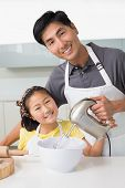 Portrait of a young man with his daughter using electric whisk into bowl in the kitchen at home