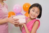 Close-up side view of a woman giving gift box to a little girl at a birthday party