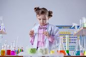 Concentrated girl looks at evaporation of reagent