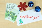Euro banknotes as gift at New year on wooden table close-up