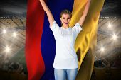 Pretty football fan in white cheering holding colombia flag against vast football stadium with fans
