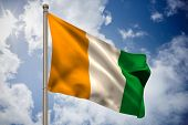 Ivory coast national flag on flagpole against bright blue sky with clouds
