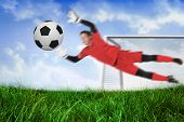 Fit goal keeper jumping up saving ball against field of grass under blue sky