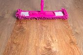 stock photo of disinfection  - close up of wooden floor with pink cleaning mop  - JPG