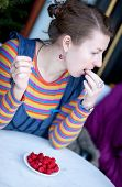 Young Girl In Bright Clothes Eating Raspberry
