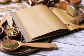 Different spices and cook book on wooden table, close up
