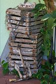 picture of lobster trap  - A stack of three lobster traps with a small old ancho resting against them in the corner of a building - JPG