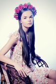 Fashion shot of a beautiful girl in a wreath of roses and light summer dress. Spring, summer romance.