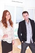 Smiling Portrait Of A Female And Male Business Executives At Office